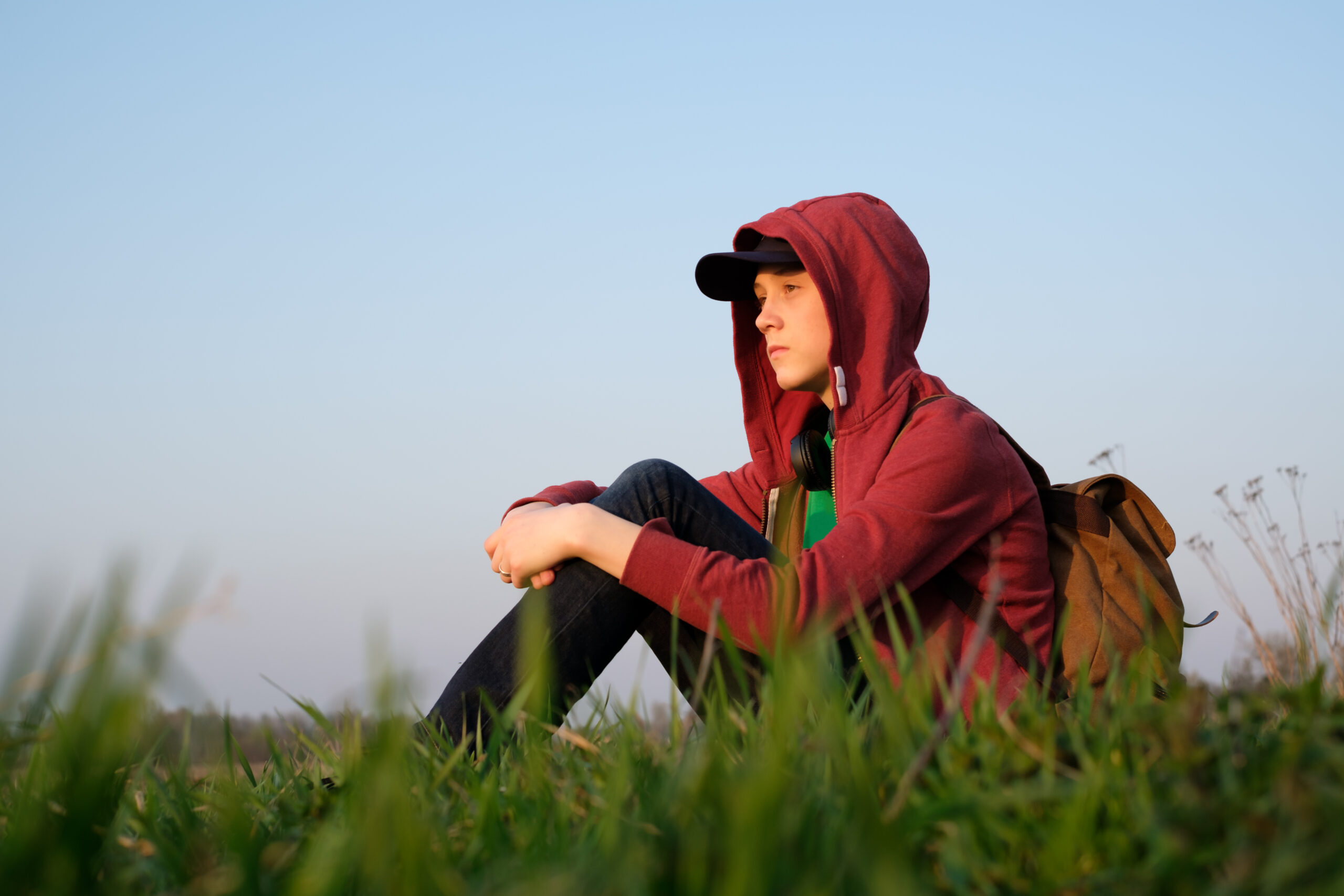 Teenager on green lawn with backpack. Happy dreamer